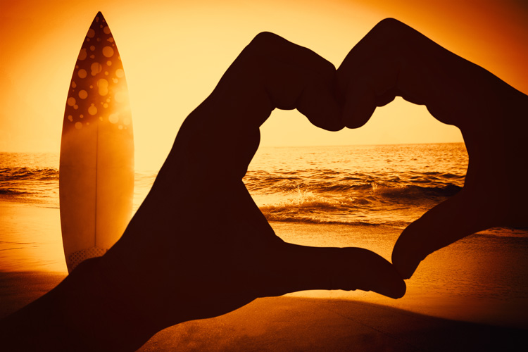 Couple making heart shape with hands against surf board standing